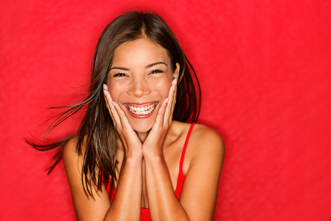 Happy girl excited. Young woman smiling very happy surprised holding head being amazed on red background. Funky young multicultural Caucasian : Chinese Asian female model joyful on red background