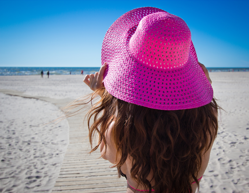 Young woman with long brown hair and big pink hat on the beach
