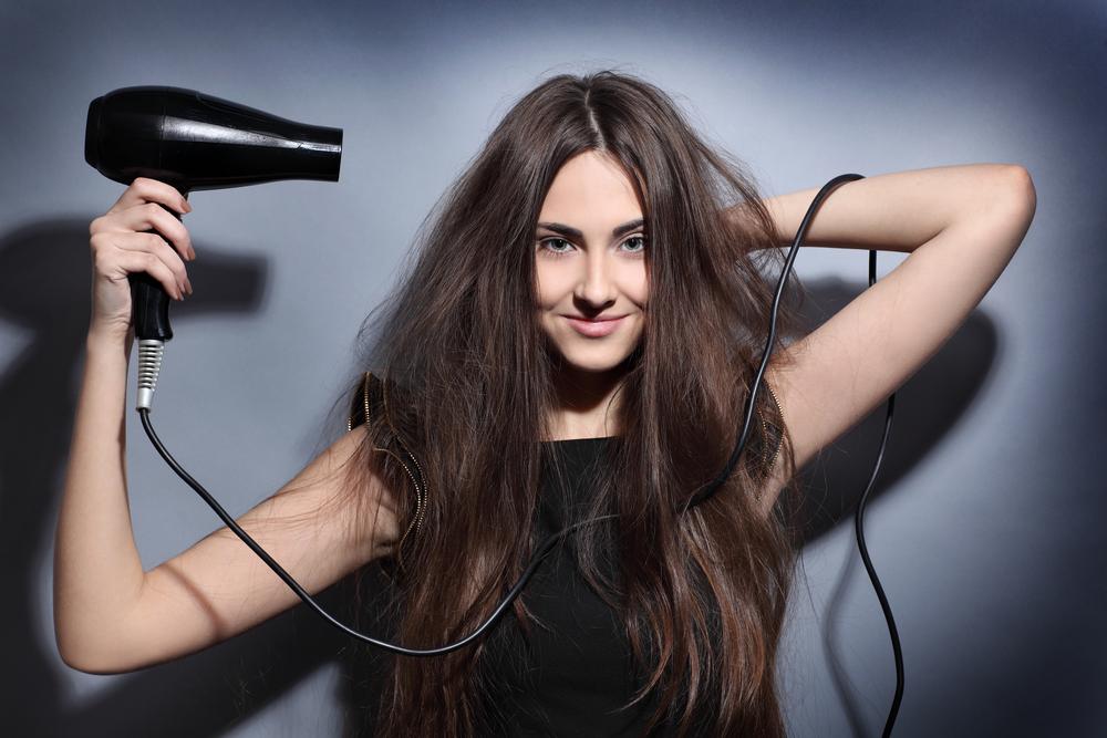 girl dries long hair hairdryer