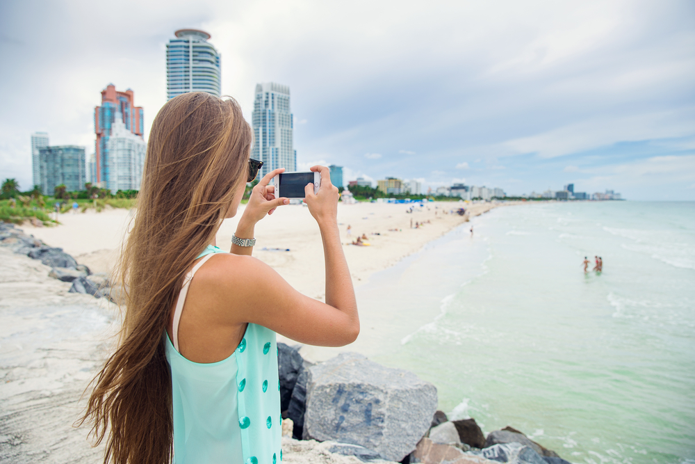 young girl model taking pictures of the ocean