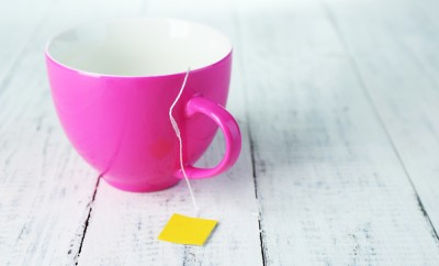 Cup with tea bag on wooden table close-up