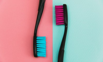 Fashion close up shot of crazy colored toothbrushes on pastel background. Minimal flat lay style