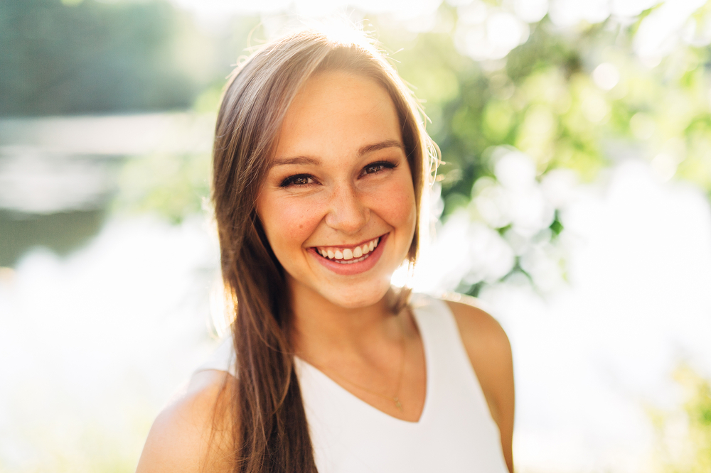 Portrait of an Attractive Young Woman Looking right at camera smiling and laughing close up