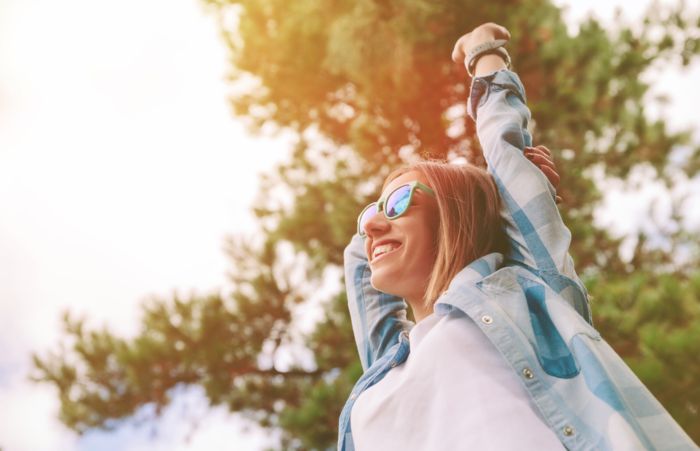 View from below of young beautiful happy woman with sunglasses and blue plaid shirt raising her arms over a sky and trees background. Freedom and enjoy concept.