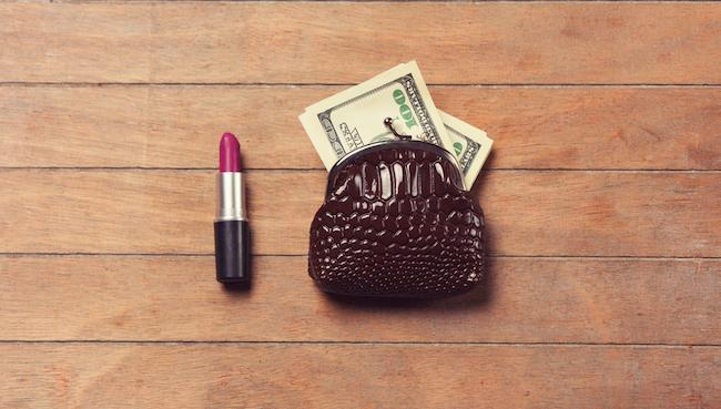 Lipstick and wallet with money on wooden background