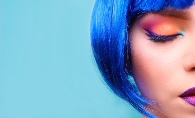 Beautiful girl with colorful makeup and wig on blue background