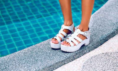 Crop photos. Female feet in white sandals with heels. It stands on the edge of the pool with blue water. Stylish image of trendy silver summer sandals