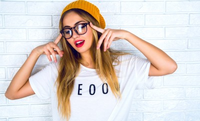 Fashion studio portrait of pretty young hipster blonde woman with bright sexy make up and glasses , wearing stylish urban t shirt and hat, White urban wall background