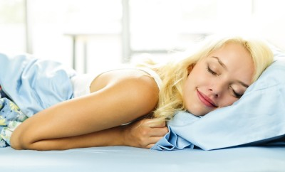 Young woman sleeping cozy in bed in the morning