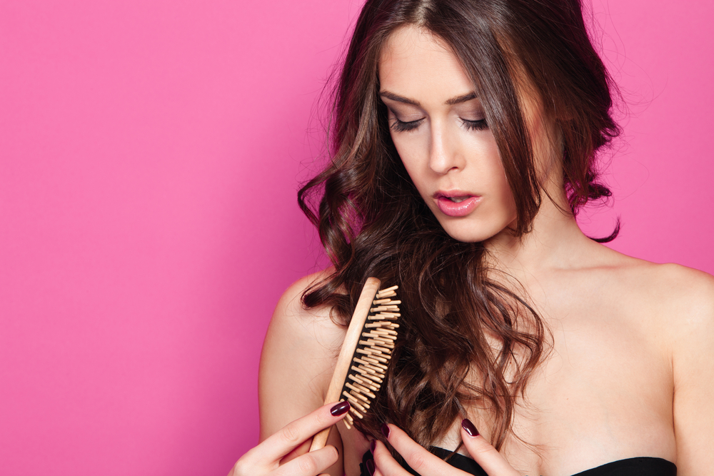 beautiful young woman brush hair studio shot pink background