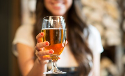 leisure, drinks, degustation, people and holidays concept - close up of smiling woman hand holding glass of draft lager beer