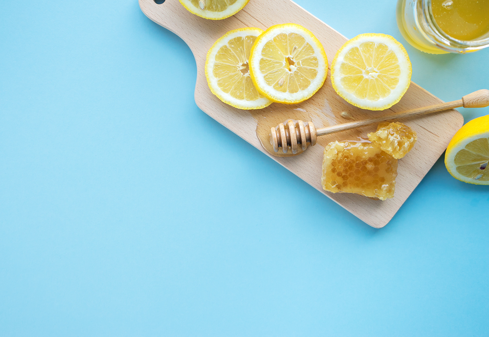 Honey in jar with honey dipper and fresh lemon on blue background