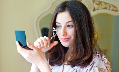 Portrait of beautiful young woman looking at the mirror using eyelash curler