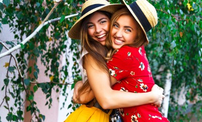 Two happy pretty young sisters, hugs smiling laughing and having funny crazy time together, bearing stylish retro vintage feminine clothes and hats. Outdoors