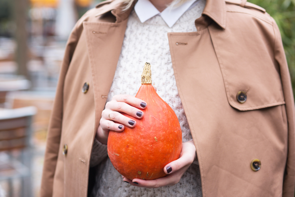 modern and stylish young women holding a hokkaido pumpkin in her hands