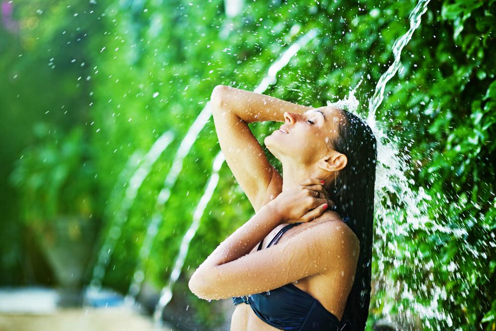 woman having shower under tropical waterfall, bali