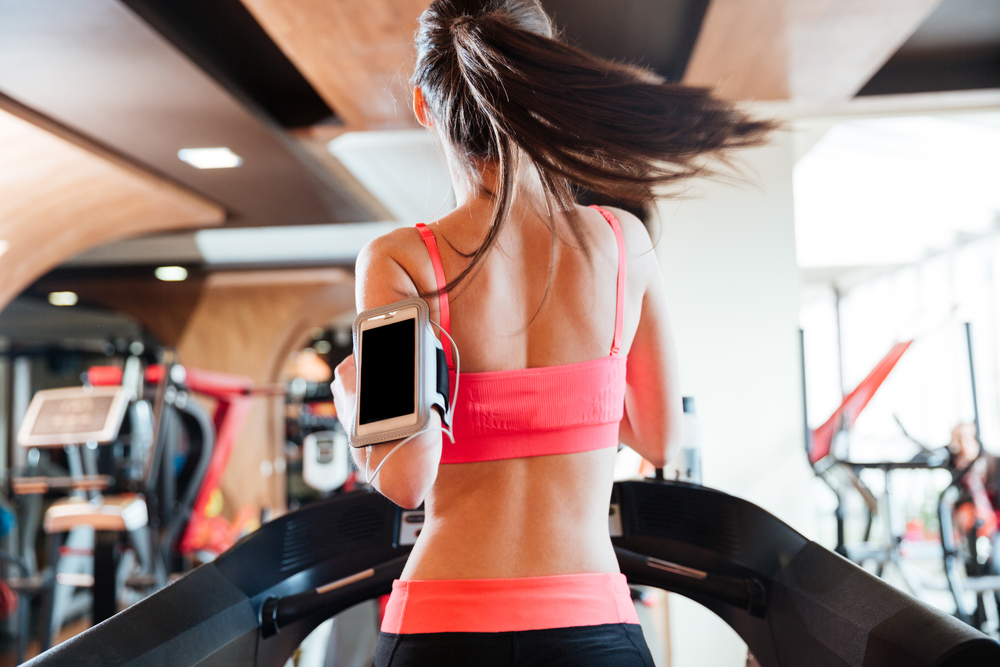 Back view of pretty young woman athlete with balnk screen smartphone running on treadmill in gym