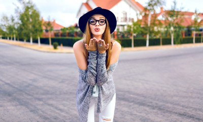 Funny autumn portrait of pretty young blonde woman, going crazy at nice autumn day, walking alone at countryside, sending air kiss, trendy hipster street style look, joy, happiness