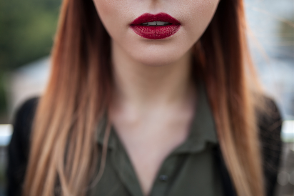 close up shot of sexy red female lips; macro shot of purple lipstick on lips of young attractive woman