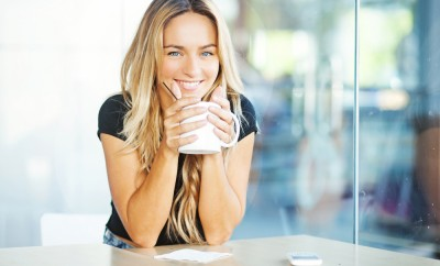woman drinking coffee in the morning at restaurant (soft focus on eyes)