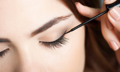 Close-up portrait of beautiful girl touching black eyeliner to her eyelid. Her eyes are closed