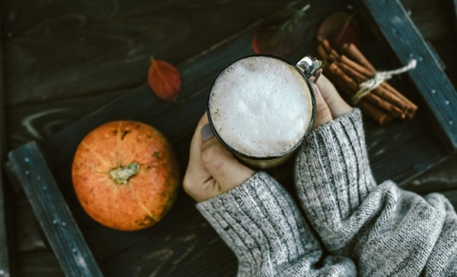 Spicy pumpkin latte on a wooden board with a sweater
