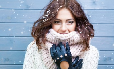 Winter portrait of young beautiful brunette woman wearing knitted snood covered in snow. Snowing winter beauty fashion concept.