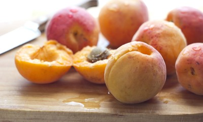 Freshly washed apricots on wooden cutting board with knife. Macro with shallow dof
