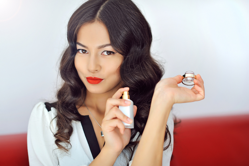 Woman with perfume, young beautiful girl holding bottle of perfume and smelling aroma