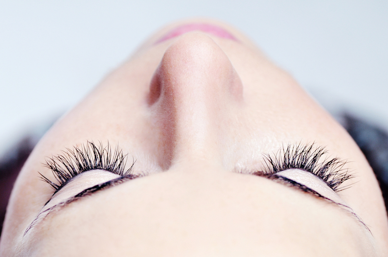 woman beautiful long eyelashes made in cosmetics salon, macro photography of pretty female eyelashes and part of face