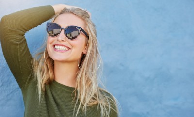 Close up shot of stylish young woman in sunglasses smiling against blue background. Beautiful female model with copy space
