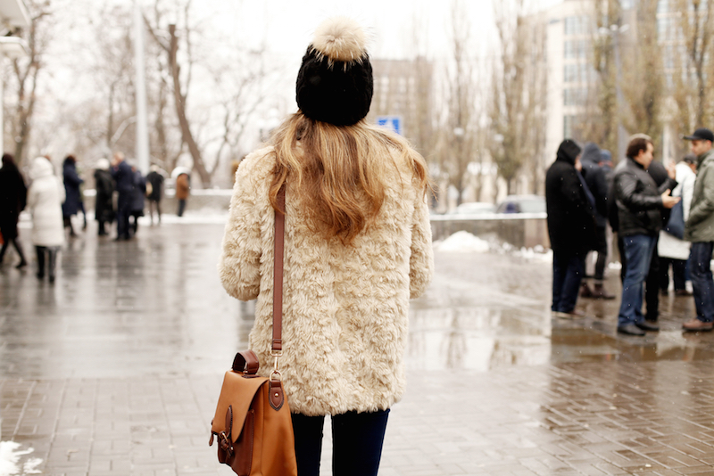 Outdoor close up portrait of fashionable woman posing on street. Model wearing stylish winter fake fur coat and beanie hat. Street style, fashion blogger outfit.