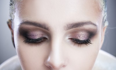 Professional beauty eyes makeup. Make up closeup. Long eyelashes and perfect skin on a gray background