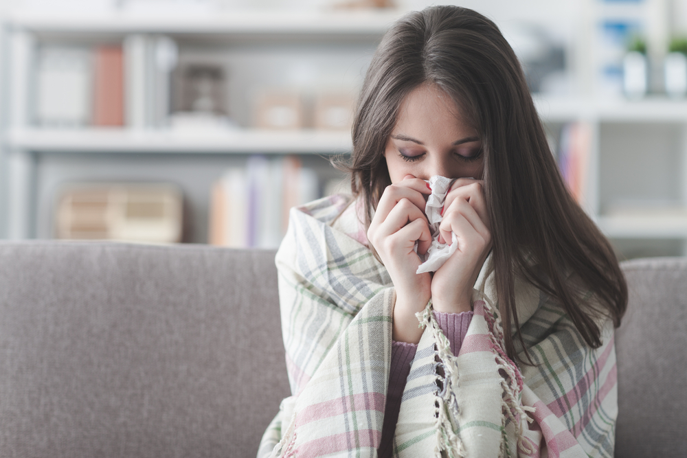 how to get rid of a cold, sick-young-woman-at-home-on-the-sofa-with-a-cold-she-is-covering-with-a-blanket-and-blowing-her-nose