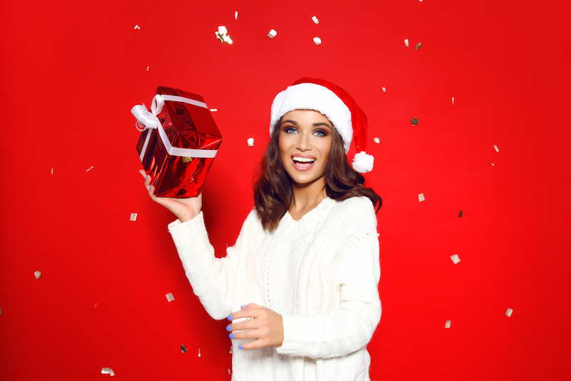 young beautiful girl stands in a white knitted sweater and santa hat against a red background behind it shatters