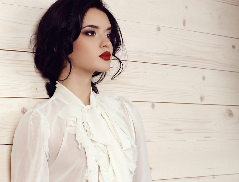 fashion studio photo of gorgeous young woman with dark hair and evening makeup,wears elegant clothes