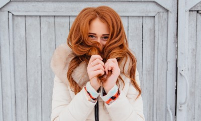 Portrait of a beautiful red hair young woman in warm clothes outdoor on the grey wooden background. Girl shows different emotions