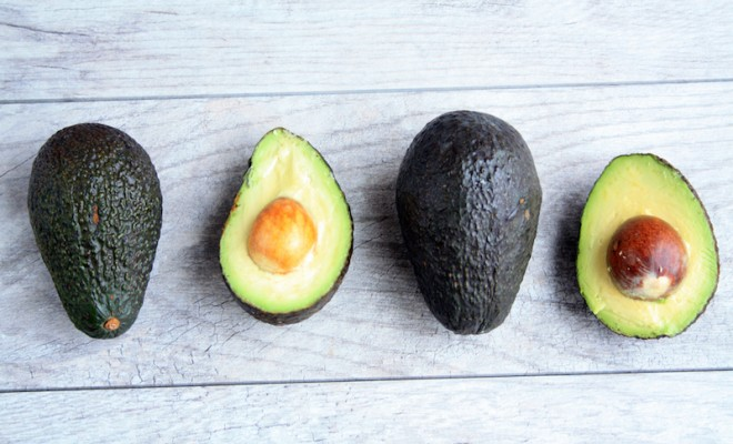 two avocados half and two whole avocados on a gray wooden background/ Half and Whole avocado/avocados