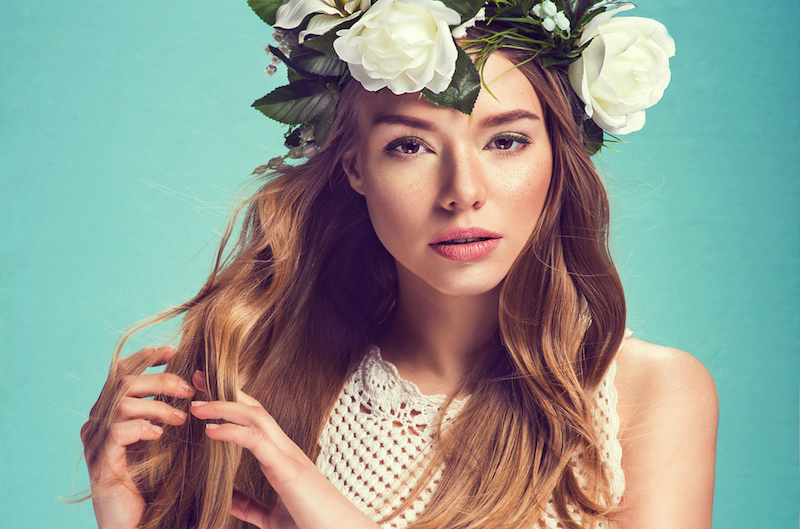 A portrait of a young beautiful woman with white flowers on the head. Spring fashion photo