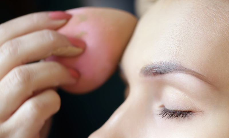 Applying foundation by sponge on face for make-up