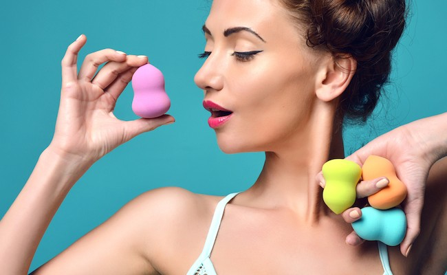 Happy surprised woman hold colorful sponge for applying foundation for make-up on face skin cares on blue mint background