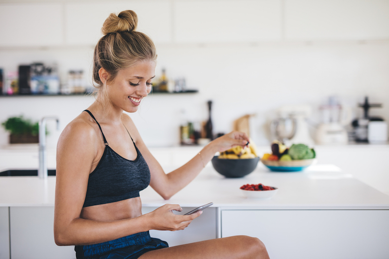 Smiling young woman sitting in kitchen using mobile phone and eating fruits. Female reading text message on her smartphone in morning.
