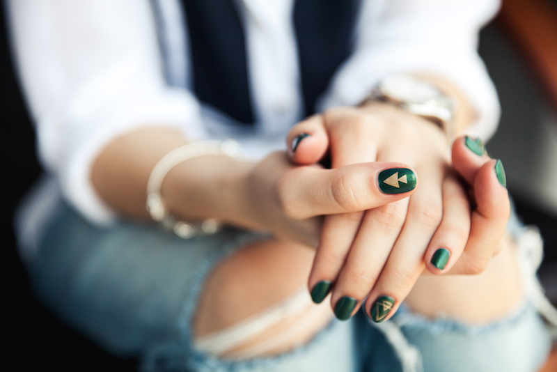 Stylish girl sitting in torn jeans and modern green nail Polish, watch, bracelet. Fashion, lifestyle, beauty, clothing.