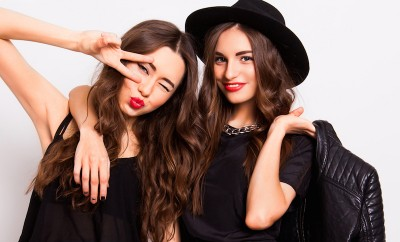 Two pretty stylish girls have fun and laughing, making grimace face . Best friends in black casual outfit posing in studio on white wall.Perfect wavy hairstyle.Bright make up.