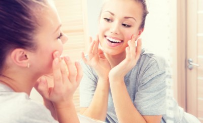 Beauty skin care. Young beautiful teenage girl touching her face before the mirror, enjoying her clean skin