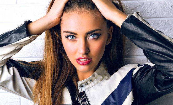Close up fashion studio portrait of stunning brunette woman with big blue eyes, full sexy lips and perfect skin, bright glamour make up, wearing biker leather jacket.