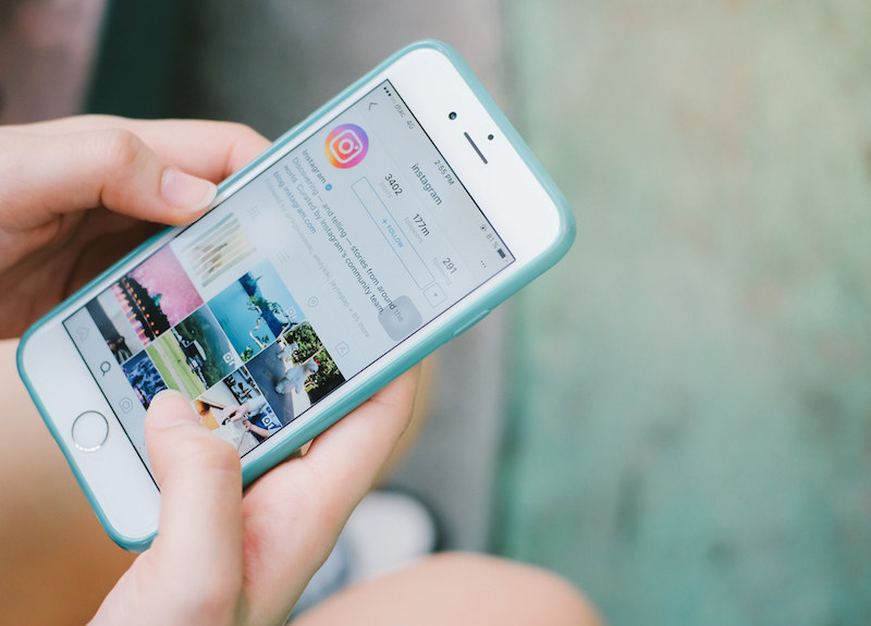 Woman hand holding Apple iPhone with Instagram application on the screen. Instagram is a photo-sharing app for smartphones.
