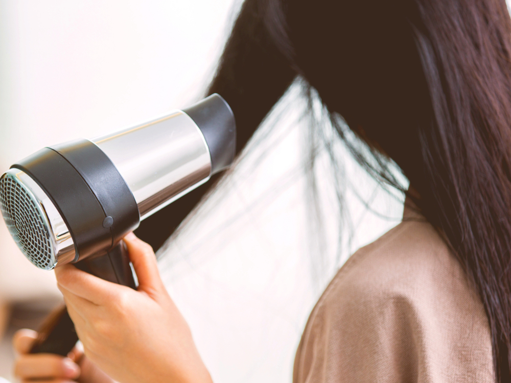at home haircut Woman with a hair dryer to heat the hair after a