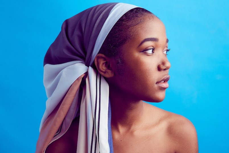 beautiful african american woman with colorful scarf blue background