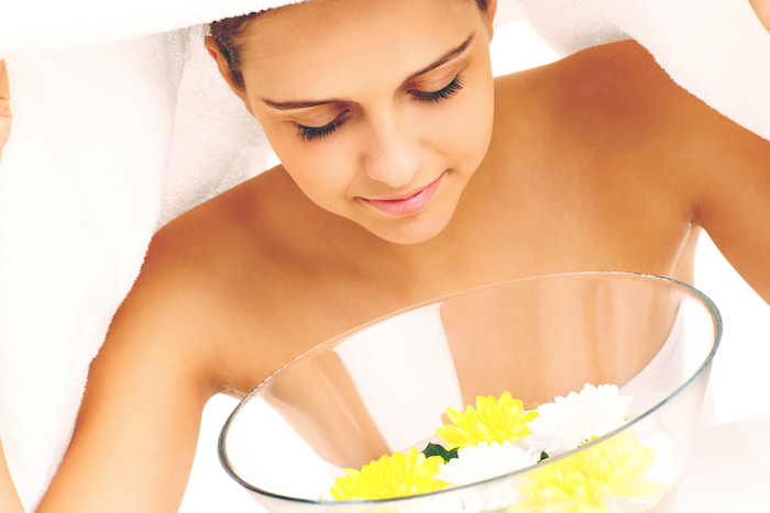 A picture of a woman doing facial treatment in spa